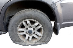Close up of a flat tire of a rusty old car centered on gravel road Stock Photography