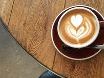 Close up flat white latte art on a wooden table against a concrete floor from above. Close up flat white on a wooden table against a concrete floor from above royalty free stock image