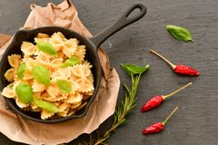 Farfalle. Close up of  Flavorful delicious   traditional italian meal pasta   farfalle with parmesan cheese   fresh basil and black pepper  in cast-iron pan Stock Images