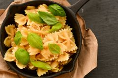 Farfalle. Close up of  Flavorful delicious   traditional italian meal pasta   farfalle with parmesan cheese   fresh basil and black pepper  in cast-iron pan Stock Photos
