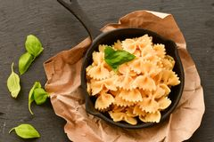 Farfalle. Close up of  Flavorful delicious   traditional italian meal pasta   farfalle with parmesan cheese   fresh basil and black pepper  in cast-iron pan Stock Photo