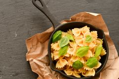 Farfalle. Close up of  Flavorful delicious   traditional italian meal pasta   farfalle with parmesan cheese   fresh basil and black pepper  in cast-iron pan Stock Image