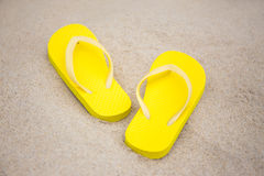 Close up of flip flops on sandy beach Stock Photography