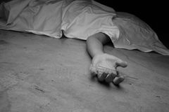 Close-up on the floor of the drugs in hand of the dead body. In Stock Photography