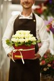 Close-up of florist holding flowers on a blurred background. Man presenting a bouquet. Decor concept. Royalty Free Stock Photography