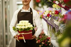 Close-up of florist holding flowers on a blurred background. Man presenting a bouquet. Decor concept. Stock Images