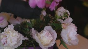 Close up florist making a bouquet of Peones stock video