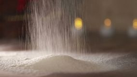 Close-up of flour through a sieve fray. Sifting flour. Baking. Ingredients and preparation stages. Wheat flour is similar to snow. Steps cooking baking and stock footage