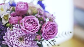 Close up of a flower bouquet being fetched to a buyer in a florist shop. Close up of a purple and pink flower bouquet being fetched to a buyer in a florist shop stock video footage