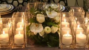 Close up of flower decor and candles on the dinner table stock photo