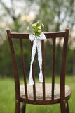 Close up of flower decorated on wedding vintage chair. Outdoor Stock Photography