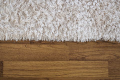 Close-up fluffy luxury carpet on laminate wood floor Stock Photography