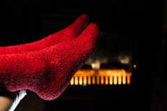 Close Up of Fluffy Red Socks by Fireplace. Close Up of Feet in Fluffy Red Socks Warming by Fireplace Stock Images