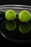 Close up of fluorescent yellow tennis balls with racket with reflection Stock Photo