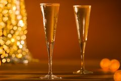 Close-Up of Fluted Champagne Glass's & Glowing Gol. Den Lights Stock Photo