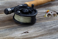 Close up of Fly Reel and Flies on Wood. Close up of fly reel, focus on front bottom of reel, with partial cork handled pole and flies blurred out on rustic Stock Photos