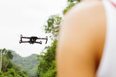 Close up of flying drone and blurred man in front in field royalty free stock photography
