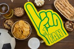 Foam hand, snacks and football on wooden table Stock Image
