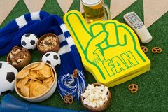 Foam hand, snacks and footballs on artificial grass Stock Photography