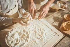 Kid forming pastry by hands. Close up focus of boy making dough ball with arms. Father helping him Royalty Free Stock Image