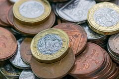 Close up focus photos of new United kingdom Pound coin, among other British coins stock photography