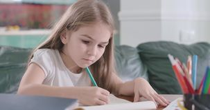 Close-up of focused Caucasian girl doing math at home. Clever schoolgirl doing homework at the table. Education