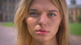 Close-up focused face of pretty caucasian blonde woman looking seriously while standing outside near buildings.  stock video