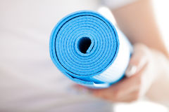 Close up: folded blue pilates mat in woman hands Stock Images