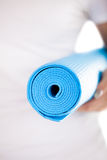 Close up: folded blue yoga mat in woman hands Royalty Free Stock Photos
