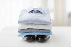 Close up of folded male shirts and shoes on table. Business, style, clothes, housekeeping and objects concept - close up of ironed and folded shirts and formal Royalty Free Stock Image