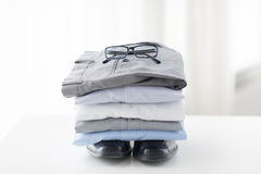 Close up of folded male shirts and shoes on table Stock Photo
