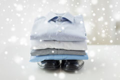 Close up of folded male shirts and shoes on table Stock Image