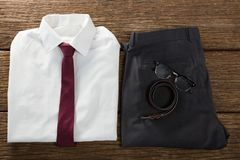Folded school uniform, belt and spectacle on wooden plank. Close-up of folded school uniform, belt and spectacle on wooden plank royalty free stock photography