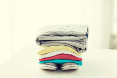 Close up of folded shirts and boots on table Royalty Free Stock Photography