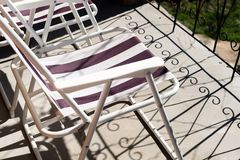 Close up of folding chair on concrete balcony floor with shadows of metal balcony fence. Relaxing on the sun in summer time stock image