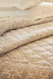 Close up of folds of luxury quilt and pillow in background Stock Images