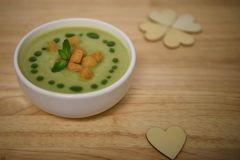 Close up food photography image of hot cooked green vegetable soup with croutons and wooden love heart decorations Stock Photo