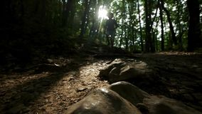 Close-up of the foot in the boot. A man hiker runs along the path in the summer forest. Hiker hiking in forest at sunset