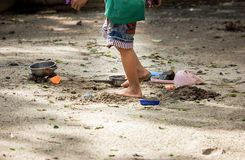Kid plan sand in the park. Close up foot of a boy are walking under light and shade on sand royalty free stock photos