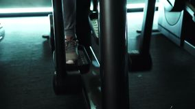 Close-up of a foot on an elliptical training machine in the gym. Man in sports shoes is engaged in exercises on modern equipment during fitness stock video footage