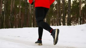 Close-up of foot running in winter on snow in sneakers through the forest. Slow motion. 120 frames per second