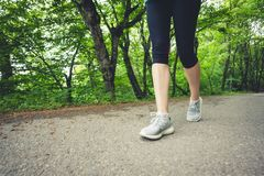 Close-up of a foot of a sporty girl in leggings and sneakers before jogging in the forest. The concept of outdoor sports stock photography