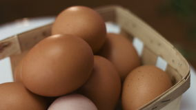 Close-up footage of a dozen of brown eggs in a wooden basket spinning around. stock footage