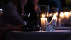 Close-up footage of elegantly decorated table at restaurant,female visitor holding a glass of red wine, fancy black stock video
