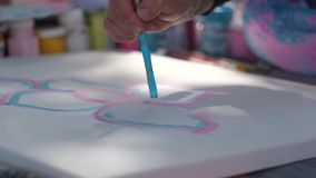Female hand holding paint brush and working with blue and pink paint. Close up footage of female hand holding paint brush and working with her paint. Outdoors stock video footage