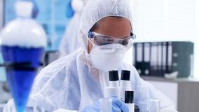 Close up footage of female scientist looking through moden microscope in research laboratory. Scientist in coverall protection equipment stock footage