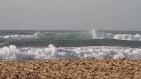 Footage of incoming waves rolling towards the sandy beach on a sunny day. Close up footage of incoming waves rolling towards the sandy beach on a sunny day stock video