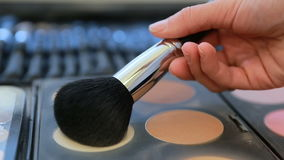 Close-up footage of a makeup palette and a make up artist using powder brush to take a color from the palette... stock video footage