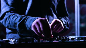 Close-up footage of a male music artists hands pushing pads and scratching on a control desk, DJ mixing music at stock footage