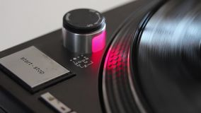 Close up footage of a person pressing the start-stop button of a vinyl player.  stock footage